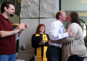 Kimberly Mumaugh, right, and A.J. McDaniel, second from right, kiss as Rev. Audette Fulbright, center, and Kevin Mumaugh look on after the pair were married outside the Laramie County Courthouse in Cheyenne. Gay couples began to apply for marriage licenses Tuesday in Wyoming, shortly after the state began to recognize same-sex unions, albeit far more quietly than in other places where bans were recently struck down.